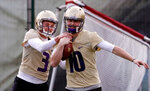 FILE - In this March 28, 2018, file photo, Washington's Jake Browning, left, tries to grab the ball from Jacob Eason during a drill for quarterbacks at the first practice of spring football for the NCAA college team, in Seattle. Eason knew his opportunity at Georgia was going to be limited if he remained with the Bulldogs. So he transferred home to Washington, even if it means he has to spend a year as a spectator. (AP Photo/Elaine Thompson, File)