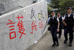 Hong Kong police officers pass by words formed with tape which read