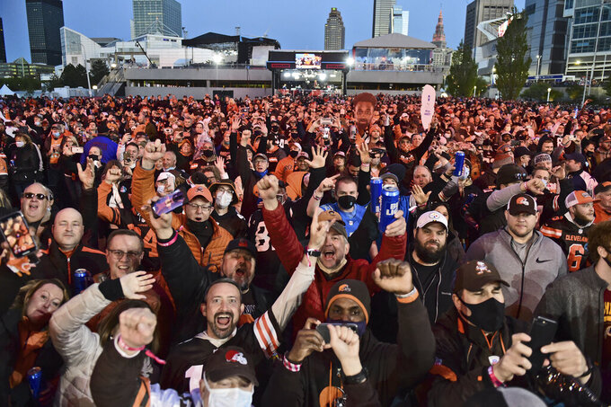 Cleveland Browns fans celebrate the second round pick, Jeremiah Owusu-Koramoah, linebacker for Notre Dame, at the NFL football draft, Friday, April 30, 2021, in Cleveland. (AP Photo/David Dermer)