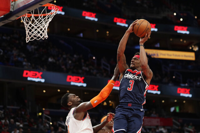 Washington Wizards' Bradley Beal (3) shoots as New York Knicks' Bobby Portis defends during the second half of an NBA basketball game Tuesday, March 10, 2020, in Washington. (AP Photo/Luis M. Alvarez)