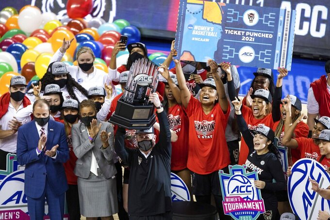 North Carolina State Head Coach Wes Moore holds up the championship trophy as his team celebrates their victory over Louisville in the championship of the Atlantic Coast Conference NCAA women's college basketball game in Greensboro, N.C., Sunday, March 7, 2021. (AP Photo/Ben McKeown)
