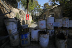 In this photo taken on Thursday Nov. 7, 2019, a Turkish military sign is seen behind barrels that block a road from the Greek Cypriot south to the Turkish Cypriots north in divided capital Nicosia, Cyprus. As the world commemorates 30 years since the fall of the Berlin Wall, the bullet-riddled sandstone walls of abandoned, crumbling homes and concrete machine gun nests dotting in Cyprus' no-man's land are a reminder of Europe's last divided country. (AP Photo/Petros Karadjias)
