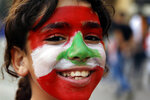 A girl painted her face with the national flag during ongoing protests against the Lebanese government, in front of the government palace in Beirut, Lebanon, Saturday, Nov. 9, 2019. Lebanon's president is meeting with several Cabinet ministers and top banking officials in search for solutions for the deepening financial and economic crisis. (AP Photo/Bilal Hussein)