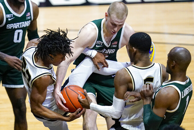 Purdue guard Jaden Ivey (23) becomes entangled with Michigan State forward Joey Hauser (20) during the second half of an NCAA college basketball game in West Lafayette, Ind., Tuesday, Feb. 16, 2021. Purdue won 75-65. (AP Photo/Michael Conroy)