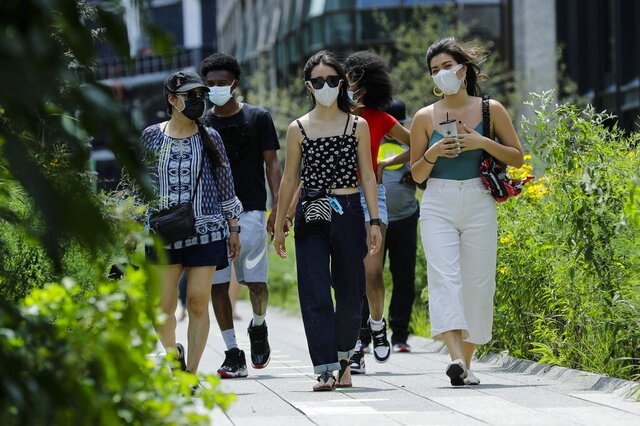 People wearing protective masks during the coronavirus pandemicwalk along the High Line Park, Thursday, July 16, 2020, in New York. The Highline opened today after having been closed the last few months during the pandemic. (AP Photo/Frank Franklin II)