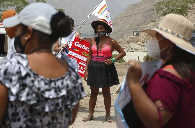 Together for Peru transgender congressional candidate Gahela Cari, campaigns in the Casachacra shanty town on the outskirts of Lima, Peru, Saturday, March 27, 2021. Like virtually all political candidates, Cari has had to face off attacks over her proposals during her campaign for a seat in Peru's congress, but unlike the rest, she has also had to fend off transphobic harassment. (AP Photo/Martin Mejia)