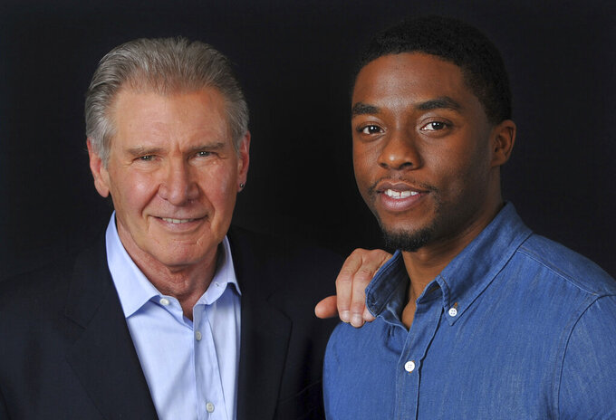 "FILE - In this Saturday, March 23, 2013 file photo, Harrison Ford, left, and Chadwick Boseman, cast members in the film ""42,"" pose together for a portrait, in Los Angeles.  Boseman, who played Black icons Jackie Robinson and James Brown before finding fame as the regal Black Panther in the Marvel cinematic universe, has died of cancer. His representative says Boseman died Friday, Aug. 28, 2020 in Los Angeles after a four-year battle with colon cancer. He was 43.  (Photo by Chris Pizzello/Invision/AP, File)"