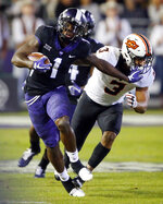 TCU wide receiver Jalen Reagor (1) gives Oklahoma State linebacker Kenneth Edison-McGruder (3) a stiff-arm after making a catch during the first quarter of an NCAA college football game in Fort Worth, Texas, Saturday, Nov. 24, 2018. (Tom Fox/The Dallas Morning News via AP)