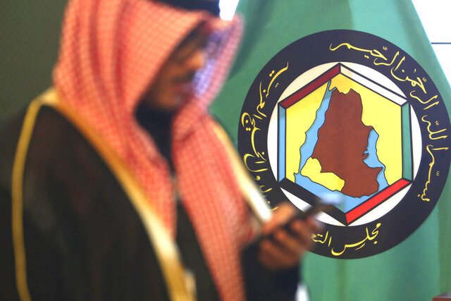 FILE - In this Dec. 5, 2017 file photo, a man looks at his mobile phone in front of the flag of the Gulf Cooperation Council, GCC, in Kuwait City. The GCC, a six-nation bloc of Gulf Arab nations torn apart by internal strife, unanimously endorsed on Sunday, Aug. 9, 2020, an extension of a United Nations arms embargo on Iran, just two months before it is set to expire. (AP Photo/Jon Gambrell, File)