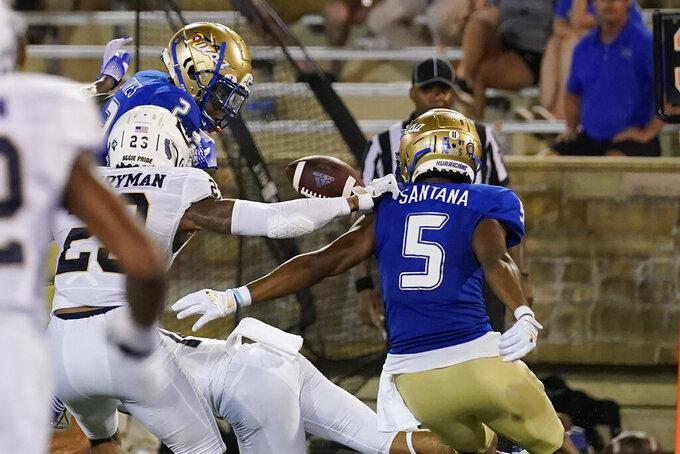 Tulsa wide receiver Keylon Stokes (2) fumbles the ball in front of UC Davis defensive back Jordan Perryman, left, and Tulsa's JuanCarlos Santana (5) during the second half of an NCAA college football game Thursday, Sept. 2, 2021, in Tulsa, Okla. (AP Photo/Sue Ogrocki)