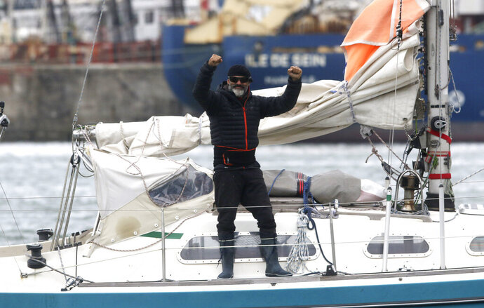 Juan Manuel Ballestero stands on his boat in Mar del Plata, Argentina, Thursday, June 18, 2020. Ballestero crossed the Atlantic on a small sailboat, setting off from the port of Porto Santo in Portugal on March 24 and finally reaching Mar del Plata on Wednesday to be reunited with his parents after flights to Argentina were cut due to the COVID-19 lockdown. (AP Photo/Vicente Robles)
