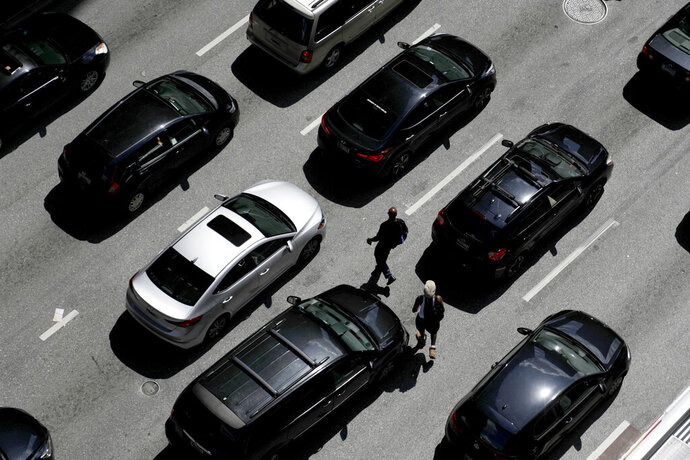 FILE - In this July 2, 2019, file photo men cross the street between vehicles waiting for a green light on East Lombard Street in downtown Baltimore. Ever since car-based SUVs passed sedans as the most popular vehicles in America a few years ago, automakers have been telling customers they get almost the same gas mileage as like-sized cars.  (AP Photo/Julio Cortez, File)