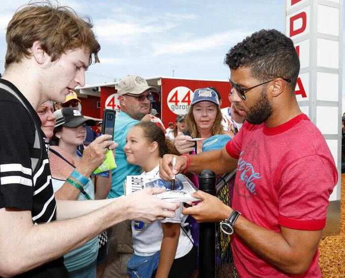 Darrell Wallace Jr., right, gives autographs to fans outside the media center where a NASCAR auto race news conference took place at Daytona International Speedway, Friday, July 5, 2019, in Daytona Beach, Fla. (AP Photo/Terry Renna)