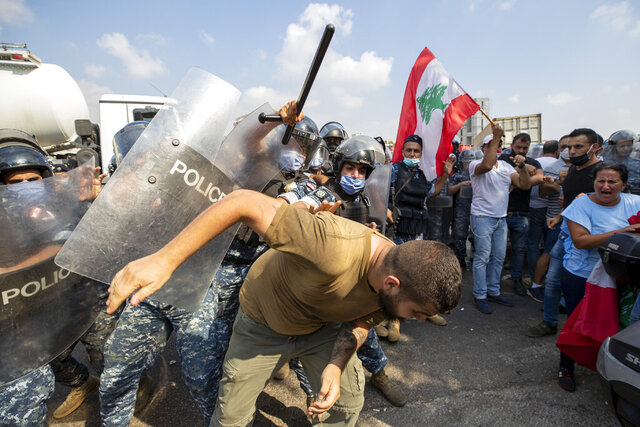 Riot police scuffle with anti-government protesters outside the Ministry of Energy and Water in Beirut, Lebanon, Tuesday, Aug. 4, 2020. Dozens of Lebanese protesters tried to storm the Ministry of Energy on Tuesday, angered by prolonged power cuts as the country grapples with a crippling economic crisis. (AP Photo/Hassan Ammar)