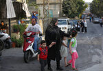 Lebanese villagers cross a street that leads to the site of an explosion that rocked a Hezbollah stronghold, in the southern village of Ain Qana, Lebanon, Tuesday, Sept. 22, 2020. The powerful explosion sent thick grey smoke billowing over the village, but the cause was not clear. (AP Photo/Mohammed Zaatari)