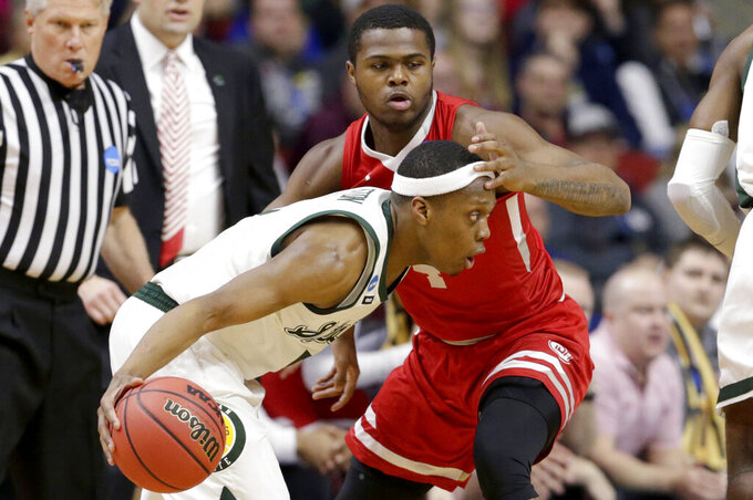 Michigan State's Cassius Winston, front, drives around Bradley's Armon Brummett, rear, during the first half of a first round men's college basketball game in the NCAA Tournament in Des Moines, Iowa, Thursday, March 21, 2019. (AP Photo/Nati Harnik)