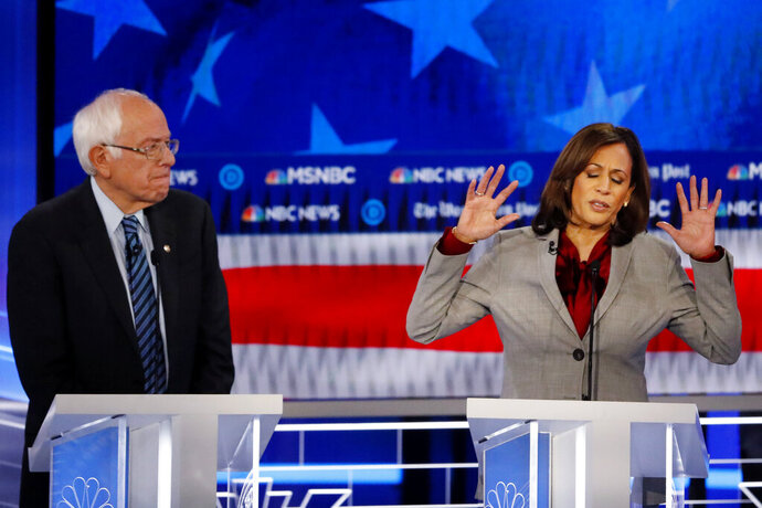 Democratic presidential candidate Sen. Kamala Harris, D-Calif., speaks as Democratic presidential candidate Sen. Bernie Sanders, I-Vt., listens during a Democratic presidential primary debate, Wednesday, Nov. 20, 2019, in Atlanta. (AP Photo/John Bazemore)