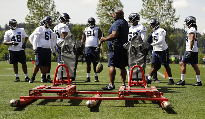 Seattle Seahawks assistant head coach Clint Hurtt, center, works with players, including rookie defensive end L.J. Collier, second from right, during NFL football rookie minicamp Friday, May 3, 2019, in Renton, Wash. (AP Photo/Ted S. Warren)