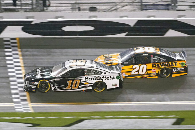 Aric Almirola (10) crosses the finish line ahead of Christopher Bell (20) to win the first of two qualifying auto races for the NASCAR Daytona 500 at Daytona International Speedway, Thursday, Feb. 11, 2021, in Daytona Beach, Fla. (AP Photo/John Raoux)