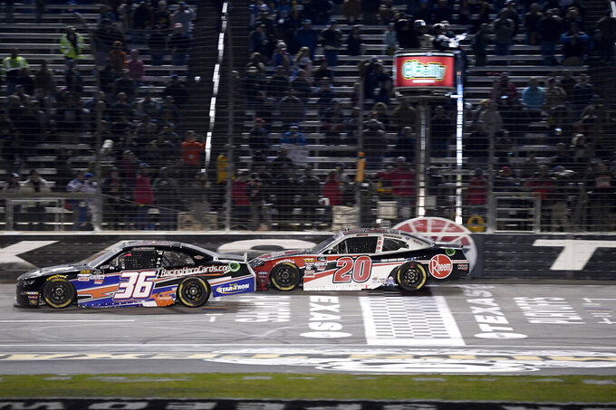 Christopher Bell (20) takes the checkered flag as he prepares to pass the lapped vehicle of Josh Williams during the NASCAR Xfinity Series auto race at Texas Motor Speedway in Fort Worth, Texas, Saturday, Nov. 2, 2019. (AP Photo/Larry Papke)