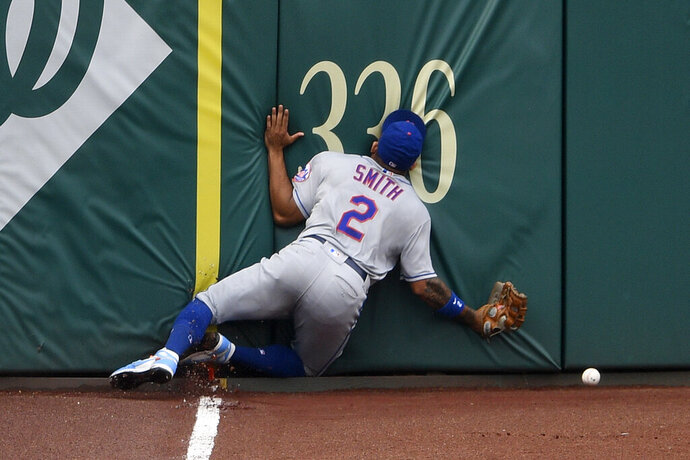 New York Mets' Dominic Smith smashes into the outfield wall while chasing a fly ball that went for an inside-the-park home run by Washington Nationals' Andrew Stevenson during the fifth inning of the first baseball game of a doubleheader, Saturday, Sept. 26, 2020, in Washington. The game is a makeup from Sept. 25. (AP Photo/Nick Wass)