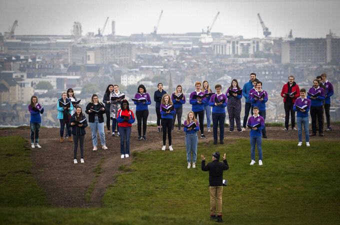 The National Youth Choir of Scotland, with founder and conductor Christopher Bell meet on Calton Hill, to sing, in Edinburgh, Monday May 17, 2021. Most of Scotland moves to Level 2 restrictions enabling up to 30 people to meet outside. The choir last met and performed together in March 2020 which is when the choir last met and performed together. (Jane Barlow/PA via AP)
