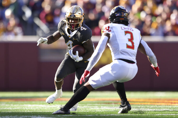 Minnesota running back Mar'Keise Irving (4) carries the ball against Maryland defensive back Nick Cross (3) during an NCAA college football game Saturday, Oct. 23, 2021, in Minneapolis. (AP Photo/Stacy Bengs)