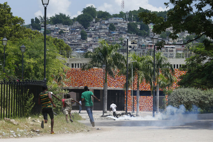 Protesters and kids run from tear gas fired by police, after a handful of demonstrators set tires alight, in the Champ de Mars park adjacent to the National Palace in Port-au-Prince, Haiti, Monday, Oct. 14, 2019. Haiti's embattled president faced a fifth week of protests on Monday as road blocks went up across the country after opposition leaders said they will not back down on their call for Jovenel Moïse to resign. (AP Photo/Rebecca Blackwell)