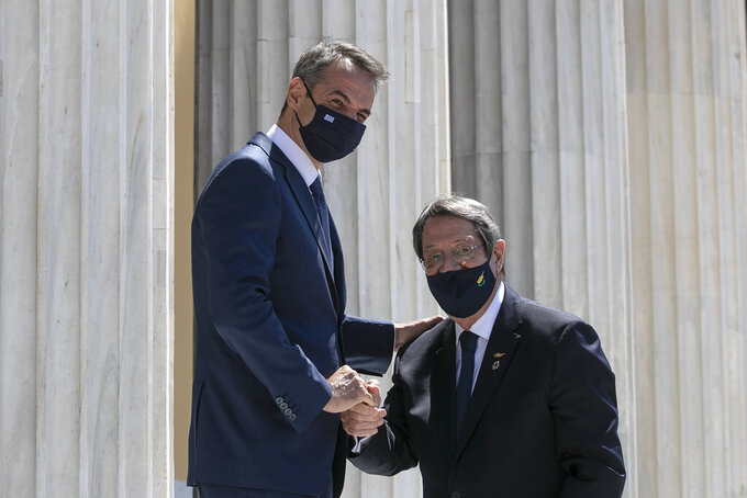 Greece's Prime Minister Kyriakos Mitsotakis, left, shakes hands with Cyrpiot President Nikos Anastasiades ahead of a meeting in Athens, on Wednesday, July 28, 2021. Greece hosts a one-day trilateral meeting of Greece, Jordan and Cyprus. (AP Photo/Yorgos Karahalis)