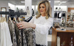 In this Tuesday, Nov. 26, 2019, photo Amy Witt, owner of the Velvet Window, adjusts merchandise for sale at her store in Dallas. Heading into the holiday shopping season, Witt opened a physical store last week to attract more shoppers than just those who have been her online customers. (AP Photo/LM Otero)
