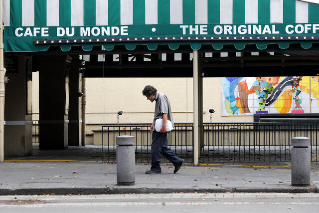 A man walks past a closed Cafe Du Monde, in the French Quarter of New Orleans, normally bustling with tourists, but now nearly completely deserted due to the new coronavirus pandemic, Friday, March 27, 2020. While rich in history and culture, New Orleans is economically poor, and the people here are not necessarily well-positioned to weather this latest storm. (AP Photo/Gerald Herbert)