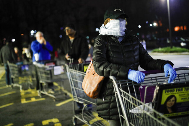 FILE- In this March 20, 2020 file photo customers wearing protective masks and gloves wait in line at a Stop & Shop supermarket in Teaneck, N.J., that opened special morning hours to serve people 60-years and older due to coronavirus concerns. The virus's rampage through the New York metro region, from the well-to-do towns along Connecticut's coastline to the bedroom communities of northern New Jersey and Long Island, offers a counterweight to the notion of the suburbs, with their plentiful open spaces, as havens safe against the coronavirus. (AP Photo/John Minchillo, File)
