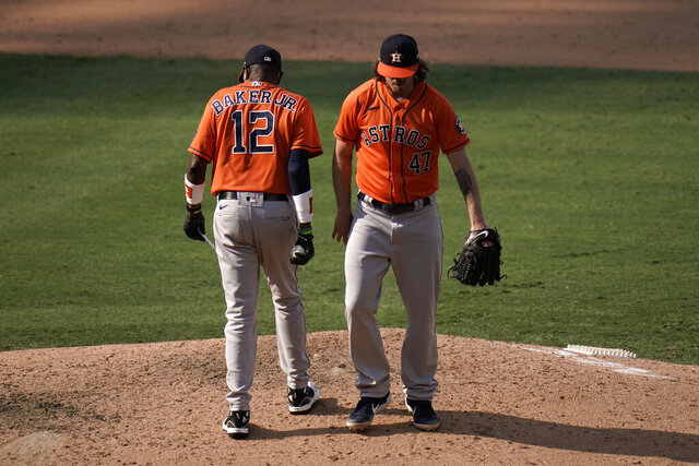 Houston Astros relief pitcher Chris Devenski, right, is relieved by manager Dusty Baker during the eighth inning of a baseball game against the Los Angeles Angels, Sunday, Sept. 6, 2020, in Anaheim, Calif. (AP Photo/Jae C. Hong)