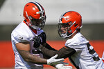 Cleveland Browns defensive tackle Tommy Togiai, left, and defensive end Romeo McKnight run a drill during an NFL football rookie minicamp at the team's training camp facility, Friday, May 14, 2021, in Berea, Ohio. (AP Photo/Tony Dejak)