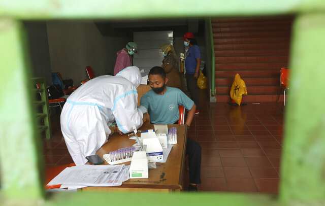 A health worker takes a blood sample from a man for a coronavirus rapid test at the Patriot Candrabhaga Stadium in Bekasi, Indonesia, Monday, Jan. 25, 2021. Indonesia has reported more cases of the virus than any other countries in Southeast Asia. (AP Photo/Achmad Ibrahim)