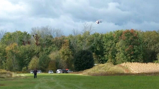 In this photo provided by Spectrum News Buffalo, a helicopter circles the site of a small plane crash near Pembroke N.Y., Friday, Oct. 2, 2020. Two people aboard the aircraft died. (Spectrum News Buffalo via AP)