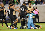 Mexico players swarm goalkeeper Guillermo Ochoa (13) after he stopped the penalty kick by Costa Rica defender Keysher Fuller to give the team the win on penalty kicks during the shootout after the the a 1-1 tie in a CONCACAF Gold Cup soccer quarterfinal Saturday, June 29, 2019, in Houston. (AP Photo/Michael Wyke)