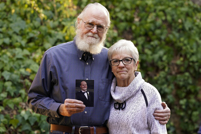 Clark McIlvain and Kathleen McIlvain hold a photo of their son, Charles McIlvain, at their home on Thursday, Dec. 3, 2020, in Woodland Hills, Calif. Charles McIlvain was one of 34 people killed when dive boat Conception caught fire and sank off the coast of California on Sept. 2, 2019. (AP Photo/Ashley Landis)
