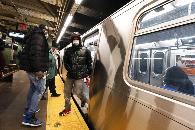 FILE — In this Nov.18, 2020, file photo, commuters wear masks stepping on and off a subway car, in New York. New York's Metropolitan Transportation Authority has approved a budget, Wednesday, Dec. 16, 2020, that doesn't include threatened service cuts and fare hikes, though officials say those options remain a possibility. (AP Photo/Mark Lennihan, File)