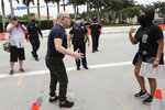 A protester, right, argues with a counter-protester, left, during a protest over the death of George Floyd  outside of the Trump National Doral, Saturday, June 6, 2020, in Doral, Fla. Protests continue over the death of Floyd, a black man who died after he was restrained while in police custody May 25 in Minneapolis. (AP Photo/Lynne Sladky)
