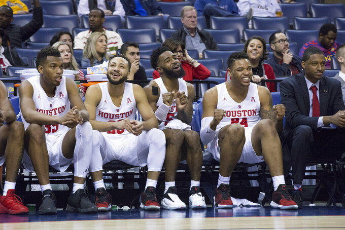 Houston players, from left, Fabian White Jr., Galen Robinson, Corey Davis Jr. and Breaon Brady celebrate a huge lead over Connecticut in the second half of an NCAA college basketball game at the American Athletic Conference tournament Friday, March 15, 2019, in Memphis, Tenn. (AP Photo/Troy Glasgow)