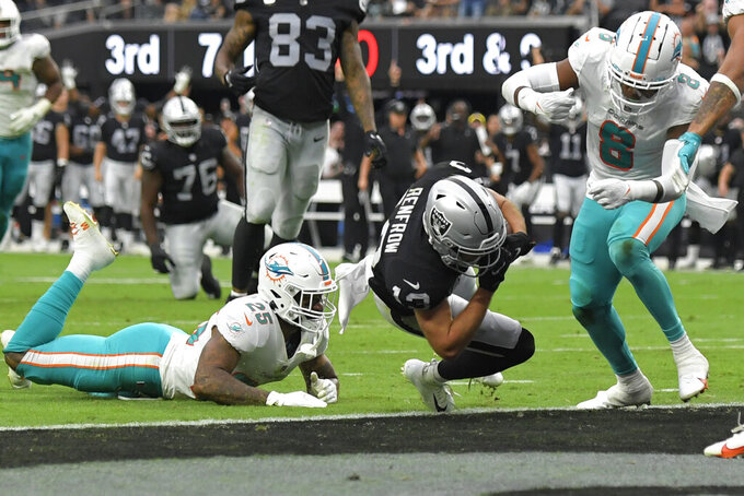 Las Vegas Raiders wide receiver Hunter Renfrow (13) scores a touchdown by Miami Dolphins cornerback Xavien Howard (25) and free safety Jevon Holland (8) during the second half of an NFL football game, Sunday, Sept. 26, 2021, in Las Vegas. (AP Photo/David Becker)