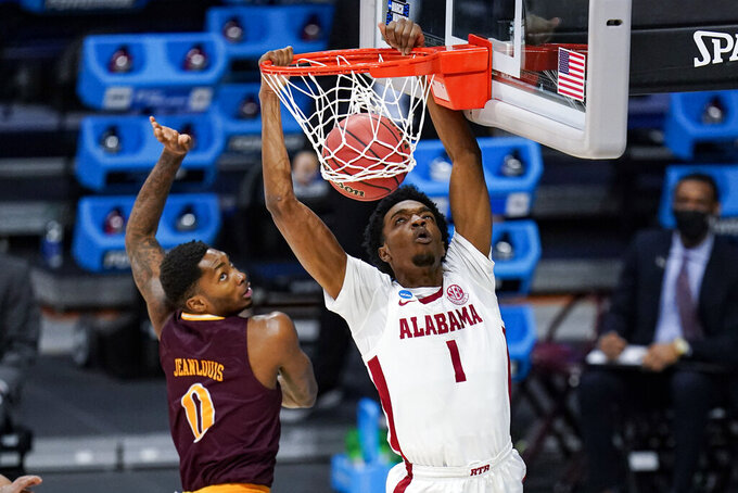 Alabama forward Herbert Jones (1) gets a basket on a dunk over Iona guard Berrick JeanLouis (0) in the first half of a first-round game in the NCAA men's college basketball tournament at Hinkle Fieldhouse in Indianapolis, Saturday, March 20, 2021. (AP Photo/Michael Conroy)