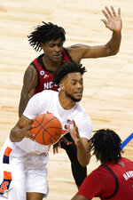 Syracuse forward Alan Griffin, middle, drives to the basket as North Carolina State guard Dereon Seabron, background, defends during the second half of an NCAA college basketball game in the second round of the Atlantic Coast Conference tournament in Greensboro, N.C., Wednesday, March 10, 2021. (AP Photo/Gerry Broome)