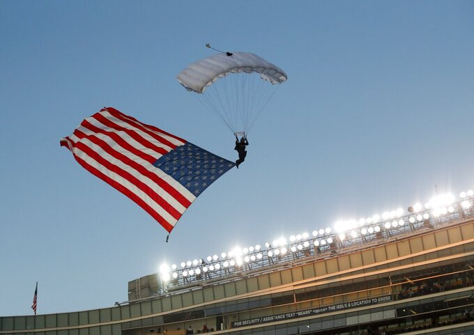A member of the U.S. Air Force parachutes into Soldier Field before an NFL football game between the Green Bay Packers and the Chicago Bears Thursday, Sept. 5, 2019, in Chicago. (AP Photo/Charles Rex Arbogast)