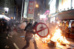 FILE - In this Aug. 31, 2019, file photo, a protester uses a shield to cover himself as he faces police in Hong Kong. Protesters and police are standing off in Hong Kong on a street that runs through the bustling Causeway Bay shopping district. Many in Hong Kong took to the streets in 2019 hoping to salvage rights of free speech and association denied to residents of mainland China, where public dissent is treated as subversive and punishable by long prison terms. (AP Photo/Jae C. Hong, File)