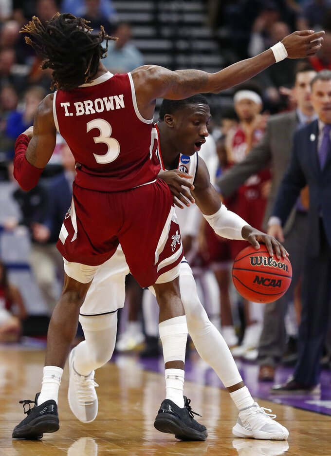 Auburn guard Jared Harper, rear, dribbles into New Mexico State guard Terrell Brown (3) in the second half during a first round men's college basketball game in the NCAA Tournament, Thursday, March 21, 2019, in Salt Lake City. (AP Photo/Jeff Swinger)
