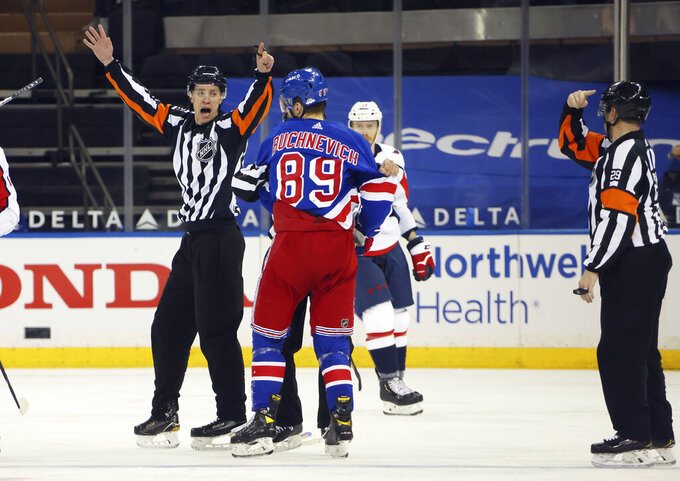 Referees TJ Luxmore and Ian Walsh (29) work the NHL hockey game between the New York Rangers and the Washington Capitals on Wednesday, May 5, 2021, in New York. (Bruce Bennett/Pool Photo via AP)