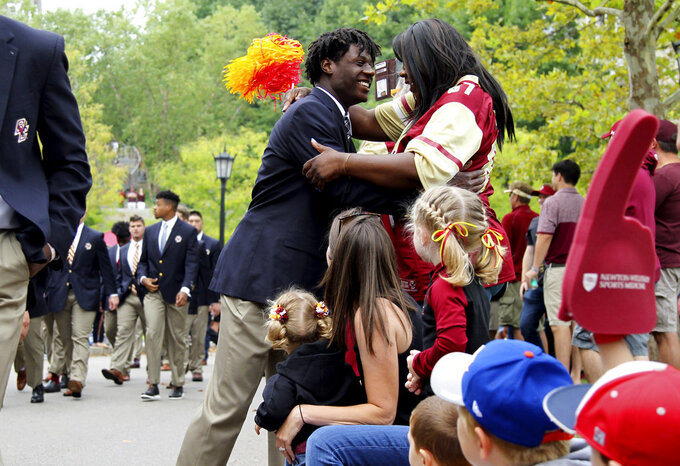 """Boston College wide receiver Noah Jordan-Williams hugs his mother Debra Williams, of Cicero, N.Y., during the """"Eagle Walk"""" before the start of a college football game against Holy Cross, Saturday, Sept. 8, 2018, in Boston. (AP Photo/Mary Schwalm)"""
