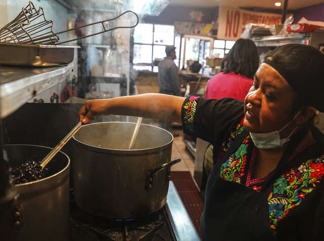 Natalia Méndez cooks in the kitchen of La Morada, an award winning Mexican restaurant she co-owns with her family in South Bronx, Wednesday Oct. 28, 2020, in New York. After recovering from COVID-19 symptoms, the family raised funds to reopen the restaurant, which they also turned into a soup kitchen serving 650 meals daily. (AP Photo/Bebeto Matthews)